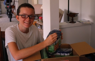 Sister Felicia opening the box of pens that just arrived in the mail.